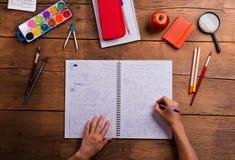 Mains de l'homme avec le carnet de maths Divers approvisionnements d'école Photographie stock libre de droits