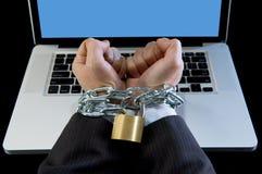 Mains de l'homme d'affaires dépendantes pour travailler le lien avec la chaîne à l'ordinateur portable d'ordinateur dans le bourr Photos stock