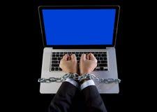 Mains de l'homme d'affaires dépendantes pour travailler le lien avec la chaîne à l'ordinateur portable d'ordinateur dans le bourr Image stock