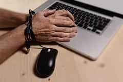 Mains de l'homme d'affaires dépendantes pour travailler le lien avec le câble de souris à l'ordinateur portable d'ordinateur dans photographie stock