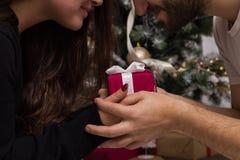 Mains de l'homme donnant le cadeau rouge de Noël Photographie stock
