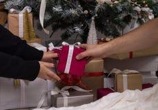 Mains de l'homme donnant le cadeau rouge de Noël Photo stock