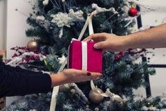 Mains de l'homme donnant le cadeau rouge de Noël Image libre de droits