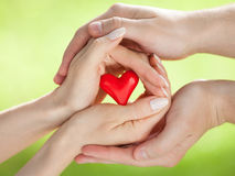 Mains de l'homme et de la femme tenant le coeur rouge Images libres de droits
