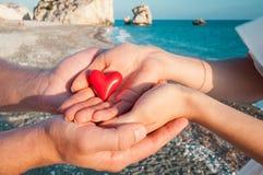 Mains de l'homme et de la femme tenant le coeur rouge Photographie stock