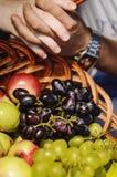 Mains de l'homme et de femme sur un panier de fruit photos stock