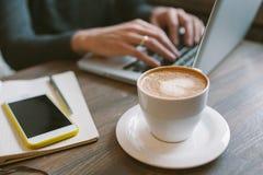 Mains de l'homme sur l'ordinateur portable avec du café et le smartphone avec le bloc-notes Image stock