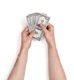 Mains de l'homme tenant des factures d'un-dollar sur le fond blanc Photo libre de droits