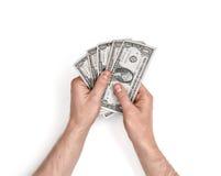 Mains de l'homme tenant des factures d'un-dollar sur le fond blanc Photographie stock