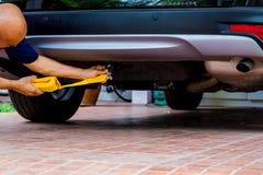 Mains de l'homme tenant la courroie jaune de remorquage de voiture avec la voiture photos libres de droits