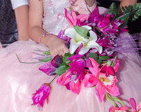 Mains de la fille dans une robe rose avec un bouquet des fleurs artificielles à un mariage Photographie stock libre de droits