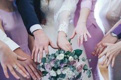 Mains de la jeune mariée et des amis avec le bouquet Photo libre de droits