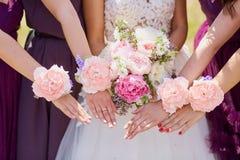 Mains de la jeune mariée et de l'amie avec les fleurs décoratives Photos stock