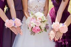 Mains de la jeune mariée et de l'amie avec les fleurs décoratives Photo libre de droits