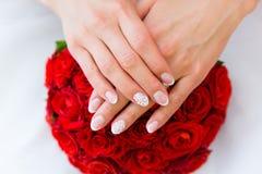 Mains de la jeune mariée sur le bouquet de mariage Images libres de droits