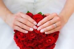 Mains de la jeune mariée sur le bouquet de mariage Photos stock