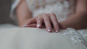 Mains de la jeune mariée sur la robe de mariage banque de vidéos