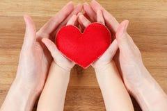 Mains de la mère et du fils tenant le symbole de coeur Images stock