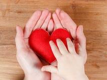 Mains de la mère et du fils tenant le symbole de coeur Image stock