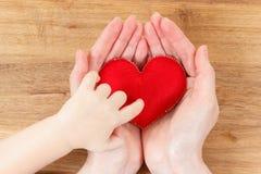Mains de la mère et du fils tenant le symbole de coeur Photo stock