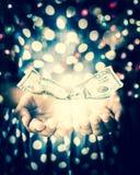 Mains de la sorcière dans une chambre noire créant un charme avec le dollar US n images stock