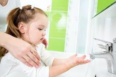 Mains de lavage d'enfant avec l'adulte photo stock
