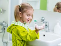 Mains de lavage d'enfant mignon dans la salle de bains photographie stock