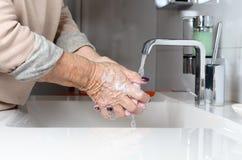 Mains de lavage de femme agée sous le robinet Photographie stock libre de droits