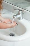 Mains de lavage de femme dans la salle de bains Image libre de droits
