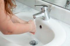 Mains de lavage de femme dans la salle de bains Images libres de droits