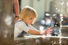 Mains de lavage de jeune fille blonde caucasienne de bébé à la fontaine de ville Photographie stock libre de droits