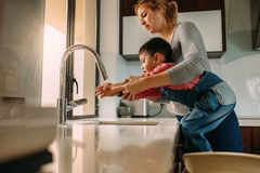 Mains de lavage de fils avec la mère dans l'évier image libre de droits