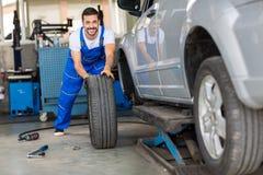 Mains de mécanicien dans l'uniforme bleu poussant un pneu noir Photos libres de droits