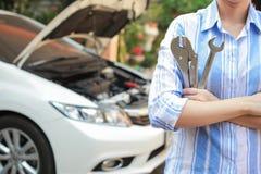 Mains de mécanicien de voiture avec le service de voiture sur le fond Photographie stock