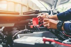Mains de mécanicien de voiture fonctionnant dans le service des réparations automatique Photos libres de droits