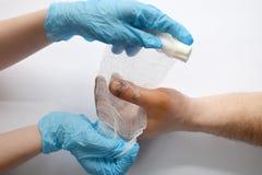 Mains de m?decins tenant la main masculine avec l'entaille ensanglant?e sur le grand doigt Examen de docteur du patient Encourage image libre de droits