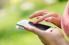 Mains de Madame sur le smartphone Image stock