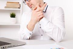 Mains de maladie de jeune homme d'affaires Fonctionnement fatigu? sur un ordinateur portable images stock