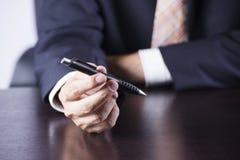 Mains de man's d'affaires tenant le stylo Photos libres de droits