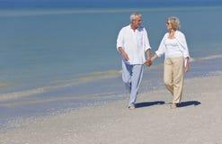 Mains de marche de fixation de couples aînés heureux sur la plage Photo stock