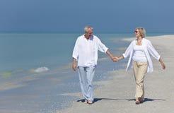 Mains de marche de fixation de couples aînés heureux sur la plage Image stock