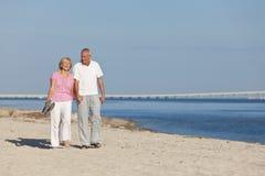 Mains de marche de fixation de couples aînés heureux sur la plage Images libres de droits