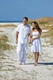Mains de marche de fixation de couples sur une plage vide Photographie stock