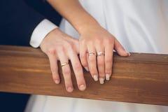 Mains de marié et de jeune mariée avec des anneaux Photo stock