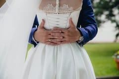 Mains de marié tenant la jeune mariée au jour du mariage Concept de famille d'amour Photographie stock libre de droits