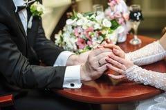 Mains de mariée et de marié avec des boucles Image stock