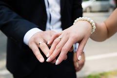 Mains de mariée et de marié avec des boucles Images stock