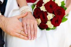 Mains de mariée et de marié avec des boucles Photographie stock libre de droits