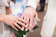 Mains de mariée et de marié avec des boucles de mariage célébrations Photographie stock libre de droits