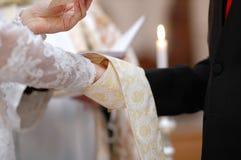 Mains de mariée et de marié et soutane du prêtre photographie stock libre de droits